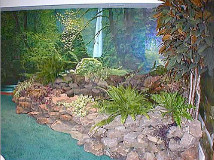 """With water gently trickling over the moss-covered rocks, and the luch vegetation """"growing"""" all around, this pond achieves its mission to create an indoor oasis."""